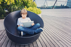 Kid using tablet computer outdoors Stock Photo
