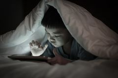 Kid using tablet while lying under blanket. Asian boy using tablet screen while lying on bed under white blanket, in the bedroom at night, bright screen light stock image