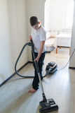 Kid using vacuum cleaner in  house Stock Photo