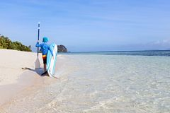 Kid on vacation. Back view of little boy in rashguard holding surf board and paddle walking at the beautiful fiji island beach, active vacation concept, copy Stock Photography