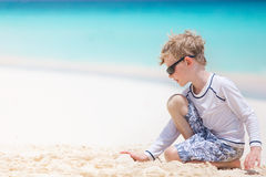 Kid at vacation. Caucasian little boy in swimsuit enjoying beach vacation and playing with sand at anguilla island, perfect caribbean beach, sun protection Royalty Free Stock Photo