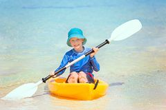 Kid at vacation. Cute smiling little boy in the kayak holding paddle enjoying active vacation at the tropical island at fiji, south pacific Royalty Free Stock Photo