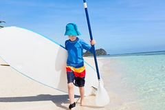 Kid at vacation. Cute smiling little boy walking with surfboard and paddle at the beach enjoying active vacation at the tropical island at fiji, south pacific Stock Image