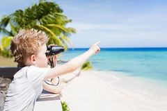 Kid on vacation. Portrait of young boy using binoculars and pointing at something with finger at beautiful tropical fiji island with turquoise lagoon in the Stock Photography