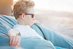 Kid at vacation. Positive little boy relaxing at bean bag, enjoying vacation and being thinkful Royalty Free Stock Images