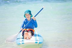 Kid at vacation. Smiling little boy in rashguard holding paddle sitting at surf board enjoying tropical vacation Stock Photo