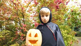 Kid in vampire costume posing with pumpkin for camera, trick or treating. Stock photo royalty free stock images