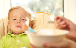 Kid is very disappointmented about porridge. Royalty Free Stock Photos