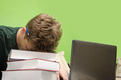 Kid very tired from homework. Sleeping on books. Tired kid, has too much homework, closeup of exhausted boy, sleeping on pile of books Stock Photo