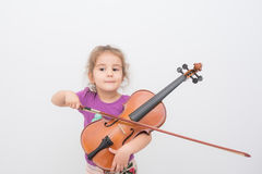 Kid violin. Blonde little kid girl trying to play violin royalty free stock photography