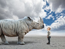Kid vs rhino. Little child and huge rhino with abstract background Royalty Free Stock Images
