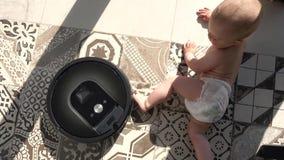 Kid vs. robot vacuum cleaner. Baby boy meets robotic vacuum cleaner on tile floor view from above stock video footage