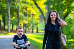 Kid Walking with His Mother in Park in Autum Colorful Background. Caption on Shirt `I am, It`s now or never, Iask myself, Why I`m here royalty free stock photos