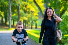 Kid Walking with His Mother in Park in Autum Colorful Background. Caption on Shirt `I am, It`s now or never, Iask myself, Why I`m here royalty free stock image