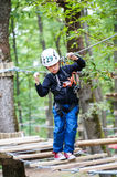 Kid walking on a logs path in adventure park Royalty Free Stock Photos