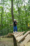 Kid walking on a logs path in adventure park Royalty Free Stock Photo