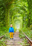 Kid walking the rails in green tunnel Stock Photos