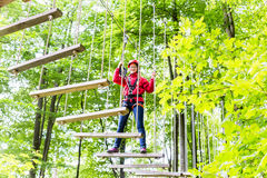 Kid walking on rope bridge in climbing course Stock Photography