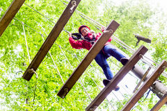 Kid walking on rope bridge in climbing course Stock Photos
