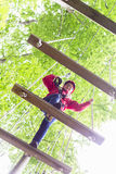Kid walking on rope bridge in climbing course Stock Images
