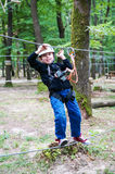 Kid walking on a wire in adventure park Stock Photography