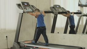 The kid walks on the treadmill. Baby is exercising in the gym near the mirror. Boy cares about his body, figure, appearance and health from the childhood. The stock footage