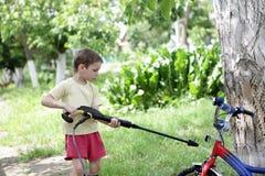 Kid washing bike Stock Photo