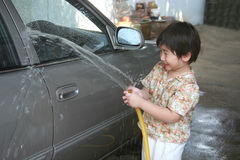 Kid washing car. In a sunny afternoon happily Royalty Free Stock Images