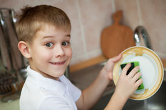 Little boy is washing dishes in the kitchen Stock Photos