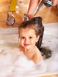 Kid washing hair by shampoo . Royalty Free Stock Image