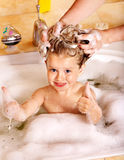Kid washing hair by shampoo . Royalty Free Stock Photo