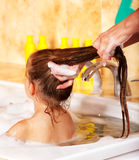 Kid washing hair by shampoo . Stock Photo
