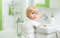 Kid washing hands in bathroom Stock Photos