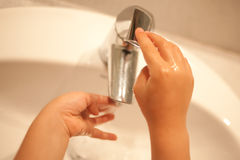 Kid washing hands under water. Royalty Free Stock Photography