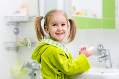 Kid washing her face and hands in bathroom. Kid child girl washing her face and hands with soap in bathroom Stock Photography