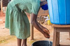 Free Kid Washing Her Hand From A Rubber Container Put In Place For Hand Washing Royalty Free Stock Images - 199042529