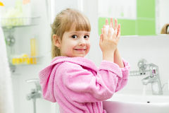 Kid washing her hands in bathroom Royalty Free Stock Photos
