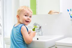 Kid washing his face and hands in bathroom Royalty Free Stock Photography