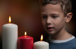 Kid watching candles. A child watching three candles burning Stock Photography
