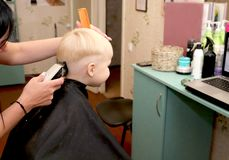 A little boy is cutting a hairdresser in the salon. The kid is watching a cartoon. Green screen on a laptop for signature royalty free stock images