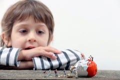Kid watching miniature people breaking an egg Stock Photos