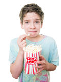Kid watching a movies. A young teen boy's expression at the movies while eating popcorn royalty free stock photos