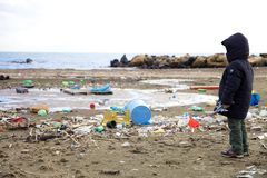 Kid watching pollution on the beach ecological disaster royalty free stock images