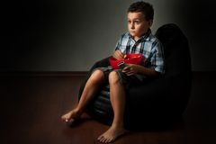 Kid watching a scary movie. Cute kid getting scared while watching a scary movie Royalty Free Stock Photos