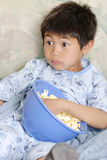 Kid watching a scary movie. With fearful expression on his face Stock Photos