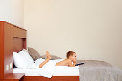 Kid watching tv in hotel room after bathing Royalty Free Stock Photo