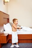 Kid watching tv in hotel room after bathing Stock Photos