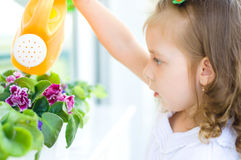 Kid watering flowers Royalty Free Stock Photos