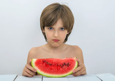 Kid with watermelon. Sad boy is having a slice of watermelon Royalty Free Stock Photo