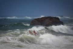 Kid in Waves near Boulder in the Ocean. Kids playing in water near a large boulder in the ocean with big waves Royalty Free Stock Photos
